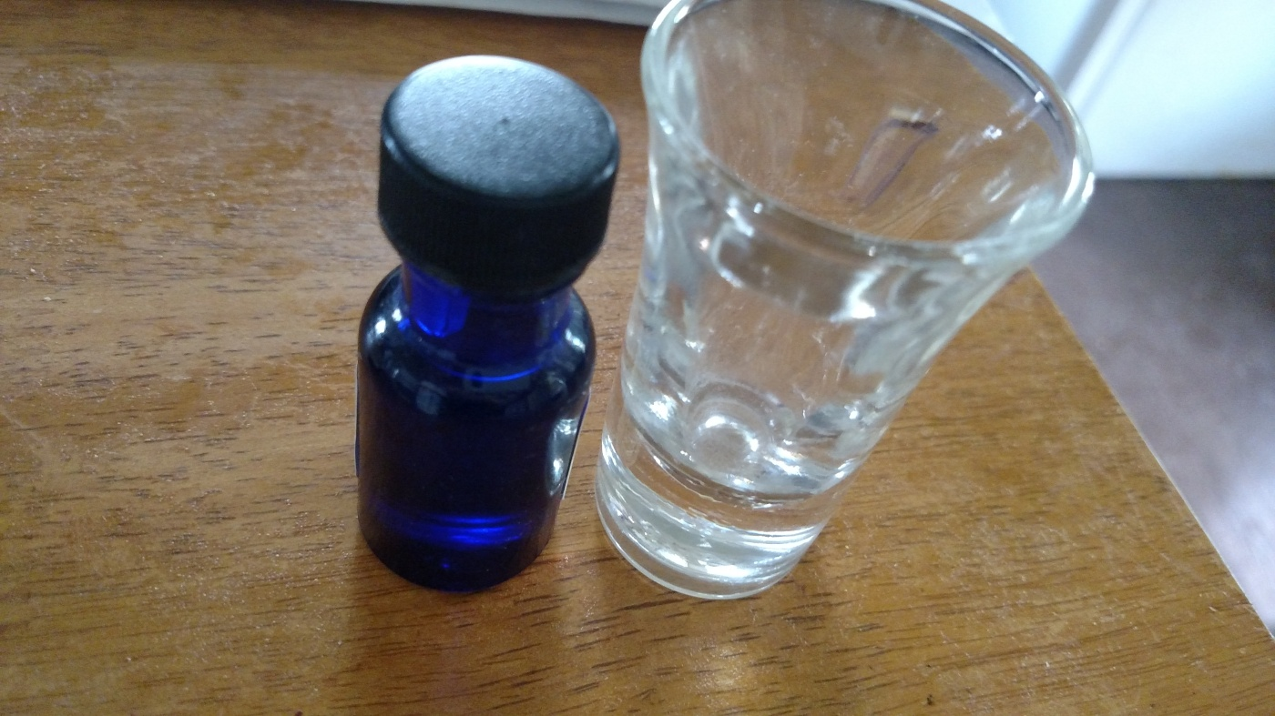 vial of liquid next to shot glass