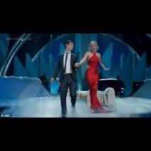 Singers Joseph Gordon Levitt and Lady Gaga are formally dressed, on a stage, singing